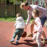 Family playing basketball in backyard